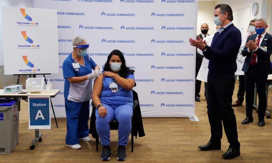 Governor Gavin Newsom applauds ICU nurse Helen Cordova as she receives the coronavirus vaccine.