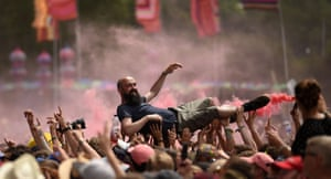 Revellers help a man crowdsurf as they watch The Slaves perform on The Other Stage at the Glastonbury Festival