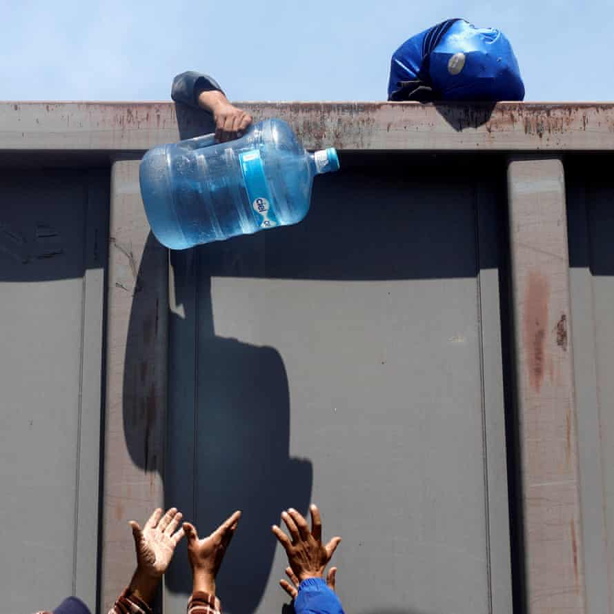 A man assing over container of water as he disembark a freight train in Tlaquepaque, in Jalisco state.