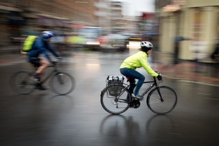 Two cyclists in hi-vis jackets and helmets