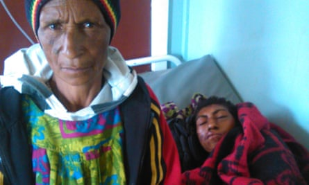 Miriam Kangup stands with her daughter, Shirley in a Papua New Guinea hospital, shortly before Shirley died. Shirley was simply walking past a group of villagers who turned on her, torturing her into confessing to sorcery.