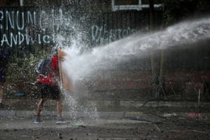 A demonstrator holds a makeshift shield to cover himself from a water cannon during a protest against the government, Santiago, Chile