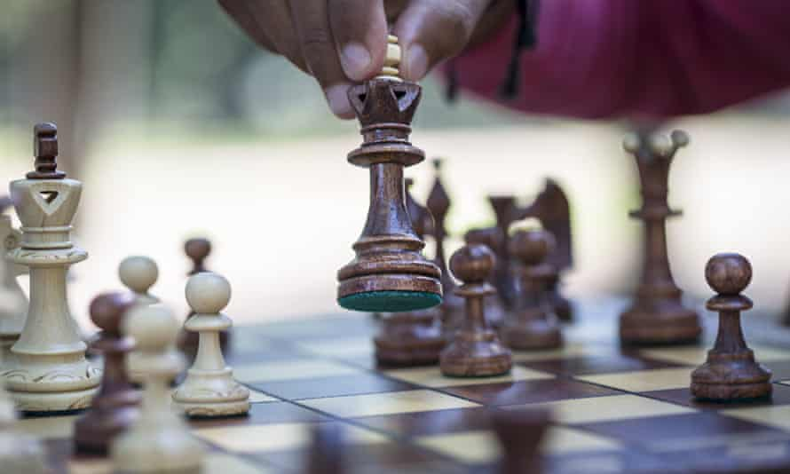 Hand moving chess piece on board.