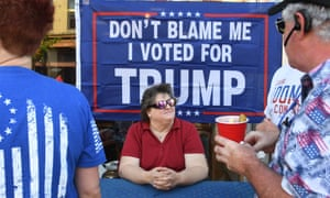 A woman sitting in front of a sign, reading 'Don't blame me, I voted for Trump'