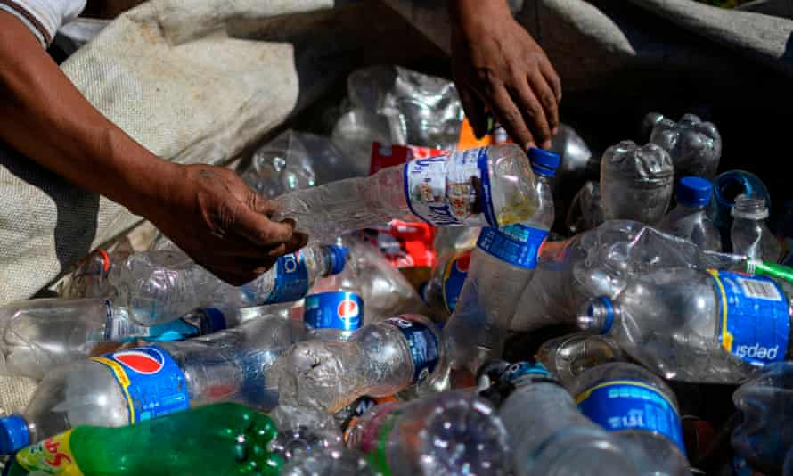A man sorts empty plastic bottles at a recycling center.