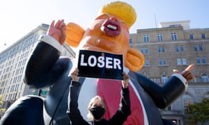 An anti-Trump protester in front of an inflatable caricature of Donald Trump in Washington DC on Friday.