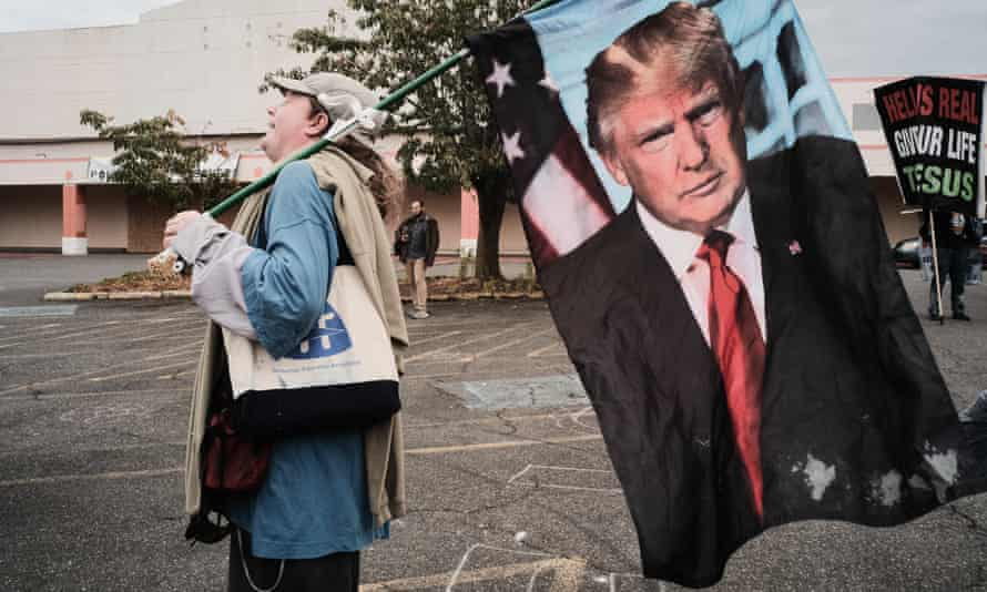 A rar right rally attendee holds a Donald Trump flag in Portland, Oregon in August.