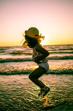 A four-year-old girl jumping for joy and dancing on the water as the sun is setting. By Aya Aisu.