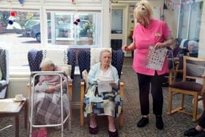 Sue, the activities co-ordinator, hands out bingo sheets.