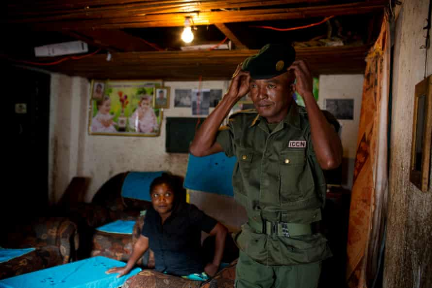 Kasereka Kioma, nicknamed Tout Terrain, a park ranger, puts on his uniform watched by his wife Jeanette, in the house they live with their children on the edge of the park near Bukavu
