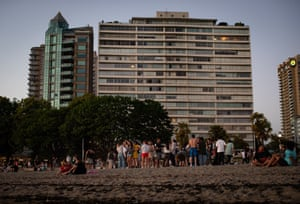 People gather at English Bay Beach, Vancouver, in the evening as temperatures cool