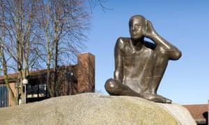 sculpture of man listening on a boulder