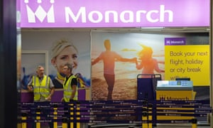 Airport staff at an otherwise deserted check-in area for Monarch Airlines at Birmingham airport