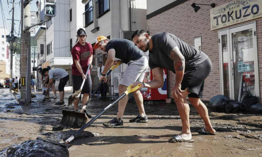 Canada team memberso clean a road in Kamaishi following the cancellation their match against Namibia because of Typhoon Hagibis.