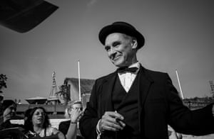 Mark Rylance, pen in hand, signing autographs on the red carpet