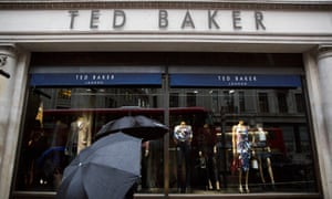 People shelter under umbrellas as they pass a Ted Baker store in London