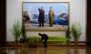 As North Korea gears up for a lavish celebration marking the 70th anniversary of its ruling Workers' Party on October 10, a man arranges flowers beneath a portrait of late North Korean leaders Kim Il-sung and Kim Jong-il in the lobby of a hotel in Pyongyang.