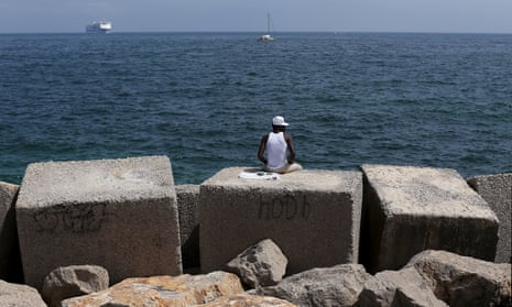 A migrant sits on a concrete block at the Palermo waterfront.