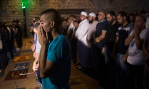 Palestinians pray in the street outside the flashpoint Lion's Gate entrance to the Haram al-Sharif-Temple Mount compound that is home to the al-Aqsa mosque,the third holiest in Islam.
