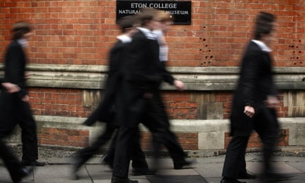 Eton boys walking past college wall