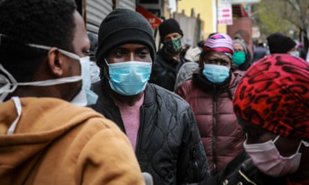 People wait for a distribution of masks and food in the Harlem neighborhood of New York City.