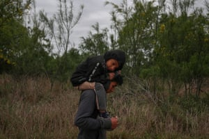 Ostavio, five, from Guatemala, rests on the shoulders of his brother Eduardo as they walk through a field after illegally crossing the Rio Grande river into the US from Mexico.