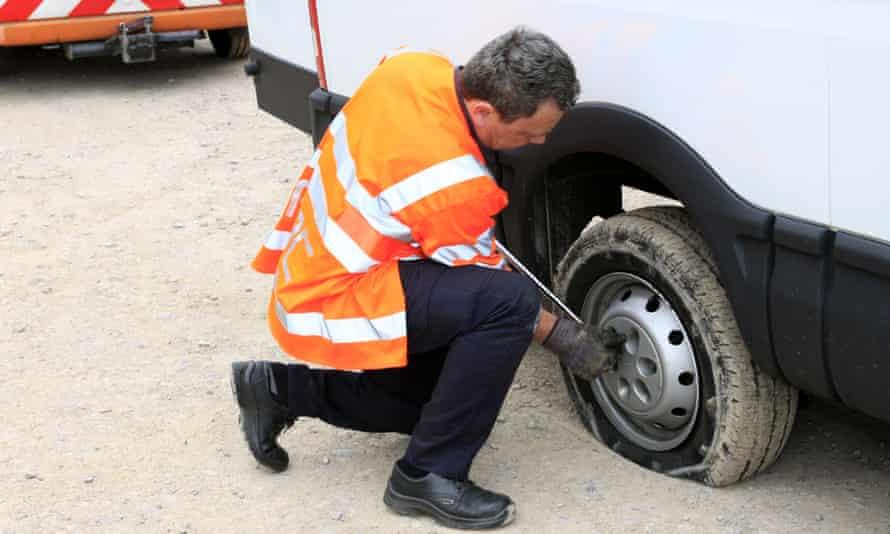 RAC breakdown man changing flat tyre