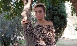 Yassmine, LGBT refugee, standing against a tree