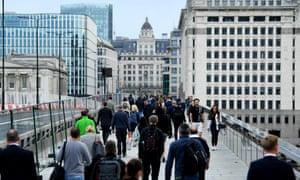 Office workers walking across London Bridge