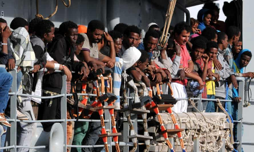 Migrants wait to disembark from the Irish naval ship Le Eithne, at the Palermo harbour, Italy.
