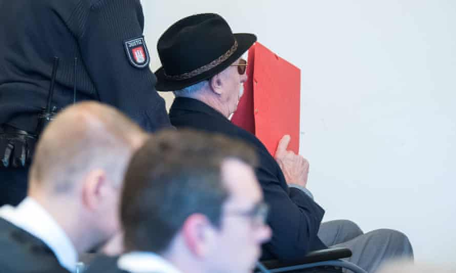 Bruno Dey using a red folder to try to cover his face during the trial in Hamburg.