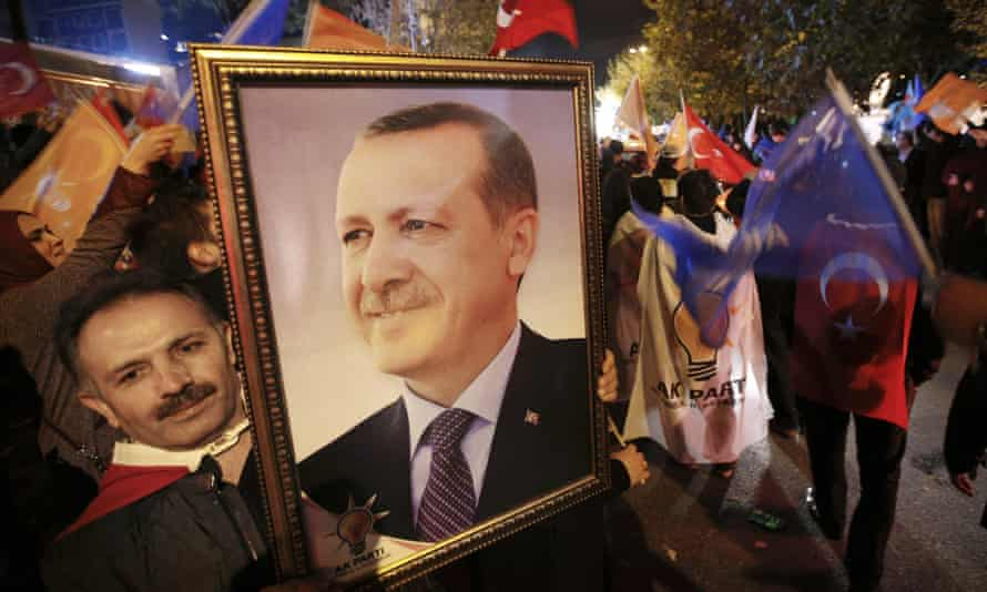 A supporter of the Justice and Development party (AKP) holds a portrait of Recep Tayyip Erdoğan.