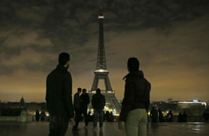 People gather as the lights of the Eiffel tower fall dark to honour the victims of the St Petersburg subway bombing.
