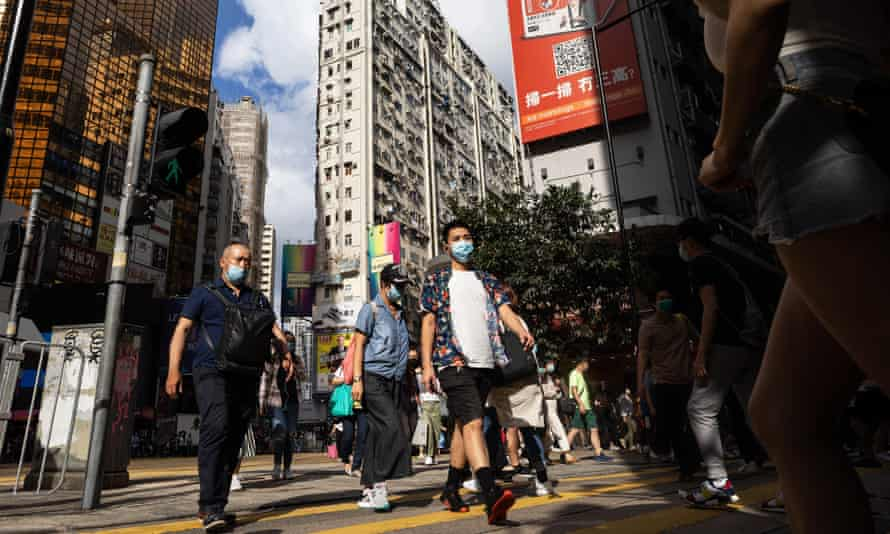Pedestrians wearing protective face masks cross an intersection on a shopping street in the Causeway Bay district in Hong Kong