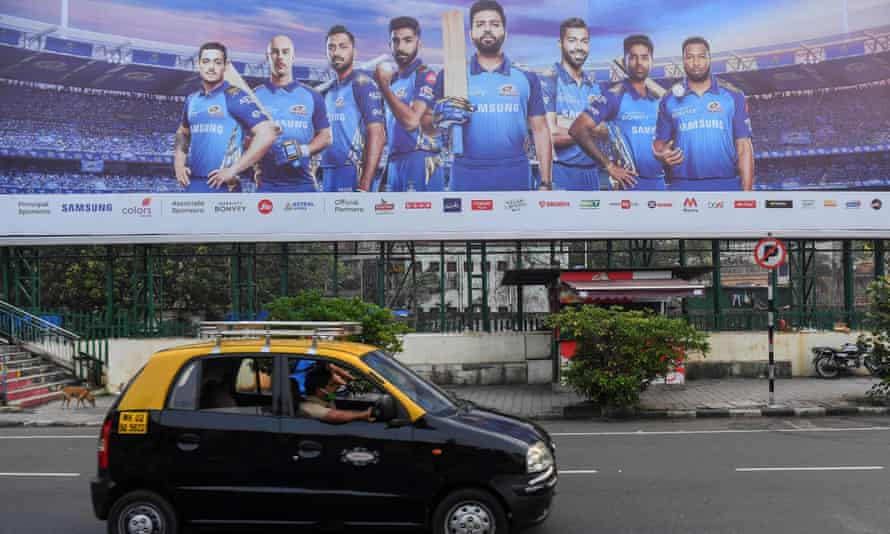 A taxi drives past a hoarding of Mumbai Indians