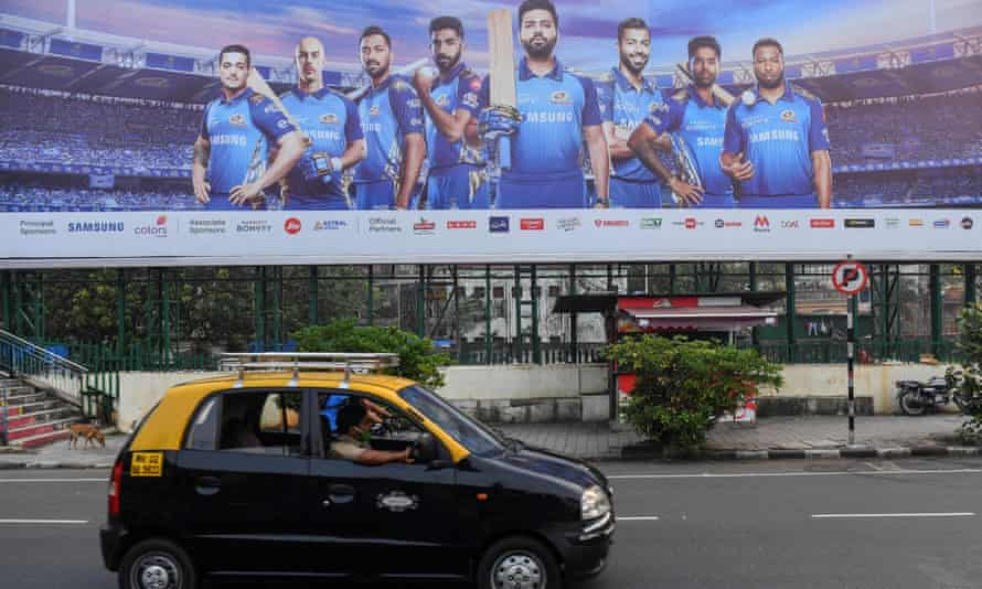 A taxi drives past an advertising hoarding of Mumbai Indians cricketers.