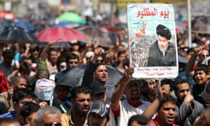A picture of Moqtada al-Sadr is held up at a protest against corruption in Sadr City, Baghdad.