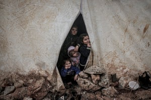 Children of Syrian families, who have been forcibly displaced due to the ongoing attacks carried out by the Assad regime and its allies, look out of a tent at a camp in Turmanin on a cold winter's day near the Turkish border in Idlib.