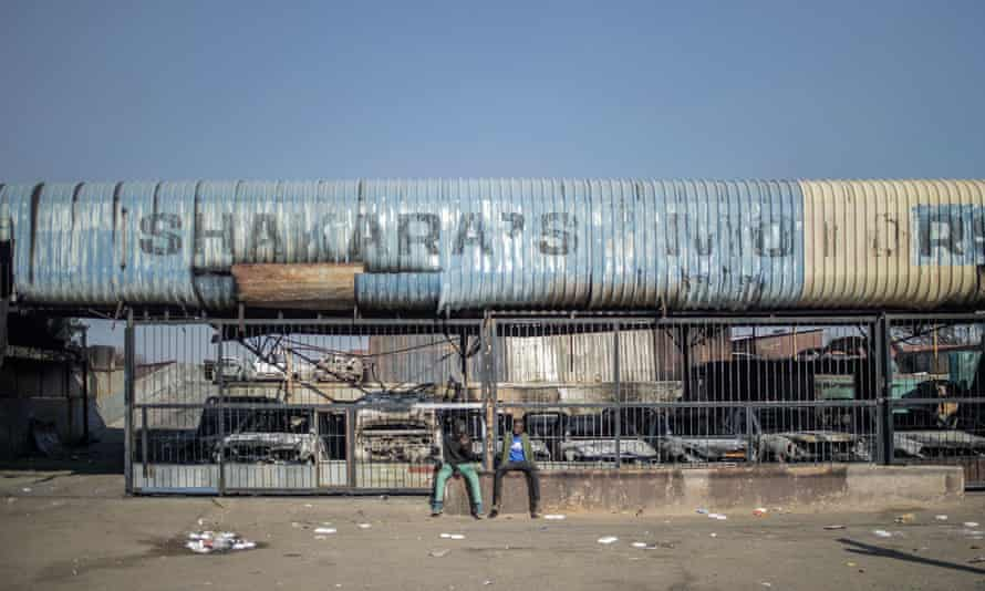 Two men sit outside a burnt-out car showroom in Johannesburg's Jeppestown district on July 11, 2021, damaged on the night of violence following protests against the imprisonment of former President Jacob Zuma.