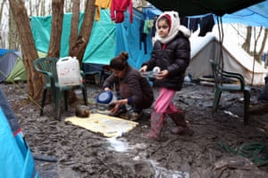 A woman washes pots with her daughter in a camp in Dunkirk, France.