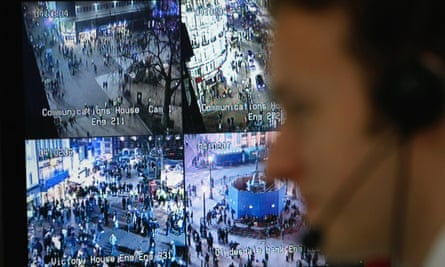 A police officer watches a television monitor looking at London's CCTV camera network.