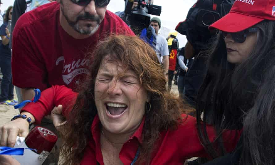Jennifer Sterling, one of the organizers of the pro-Trump rally, is helped after getting hit with pepper spray by an anti-Trump protester.