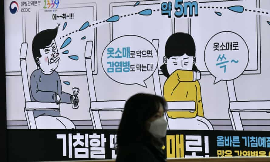 A woman wearing a face mask walks past a poster in Seoul, South Korea, showing preventative measures against infectious diseases.