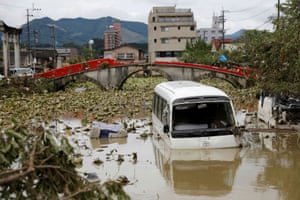 A broken bridge, an overturned vehicle and a partially submerged bus in floodwater in Hitoyoshi