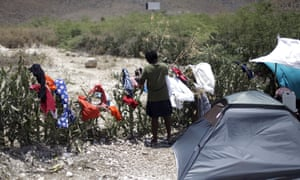 A woman picks up dry laundry at a camp for returned Haitians and Haitian-Dominicans, near the border with the Dominican Republic.