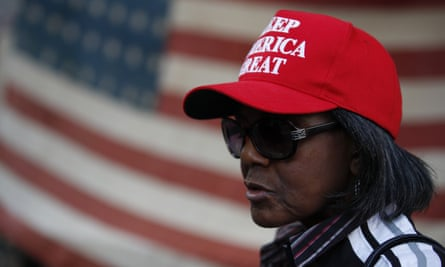 A woman stands in front of an American flag, as a handful of supporters of President Donald Trump continue to protest outside the Pennsylvania Convention Center, in Philadelphia, Tuesday, Nov. 10, 2020. (AP Photo/Rebecca Blackwell)