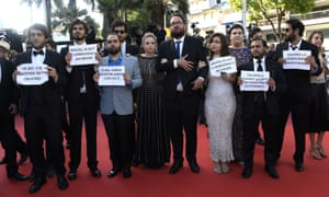 The cast and crew of Aquarius hold up signs of solidarity with the Brazilian president Dilma Rousseff at Cannes