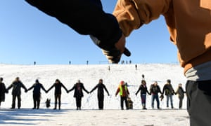 Native Americans and activists campaigning against the Dakota Access pipelilnes hold hands in prayer and solidarity on the edge of the Standing Rock Sioux reservation in North Dakota.