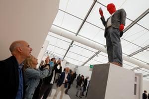 Visitors to the Frieze London admire a sculpture.