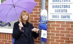 Joy Hart, former director at Bury FC, locks herself to a drainpipe near Gigg Lane in protest against the club's owner.